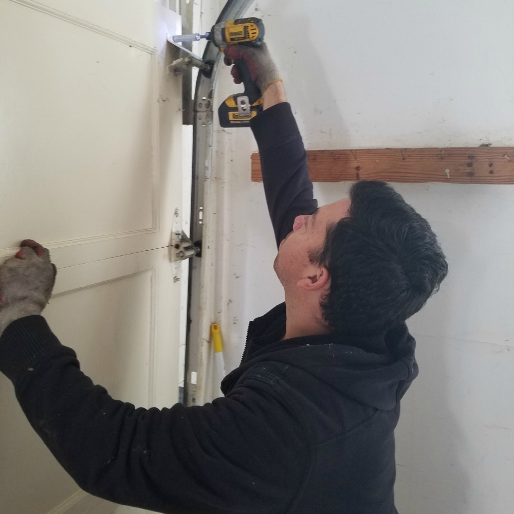 garage door repair expert makes adjustments with power tool