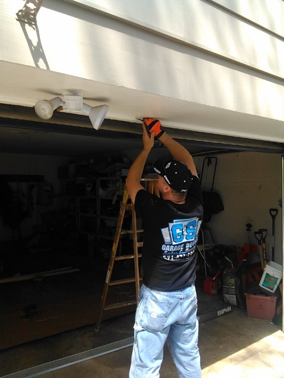 garage door repair professional adjusts installation